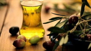 stock-footage-bottle-of-olive-oil-with-olives-rolling-in-foreground